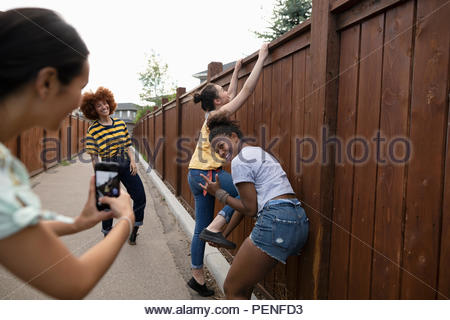 Playful teenage girl friends with camera phone climbing fence - Stock Photo