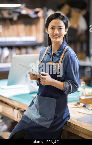 Confident leather craftswoman holding a digital tablet in studio - Stock Photo