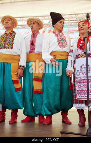Ukrainian folk choir performing at a stage. Group of elderly people wearing ethnic national costumes sings at a concert. Ukraine culture performance - Stock Photo