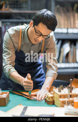 Young leather craftsman working in studio - Stock Photo