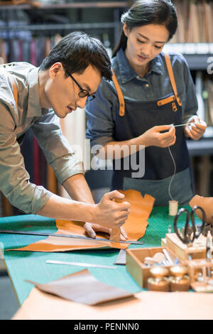 Young leather craftspeople working in studio - Stock Photo