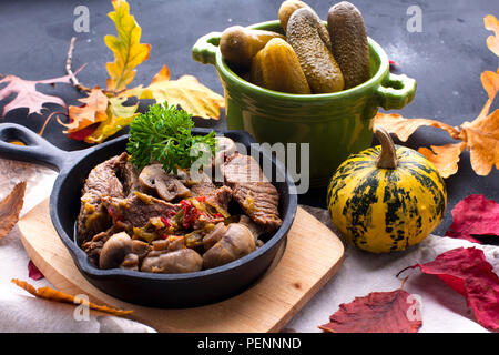fried meat with mushrooms in a frying pan. on a black background. Lunch with autumn leaves. Top view. - Stock Photo
