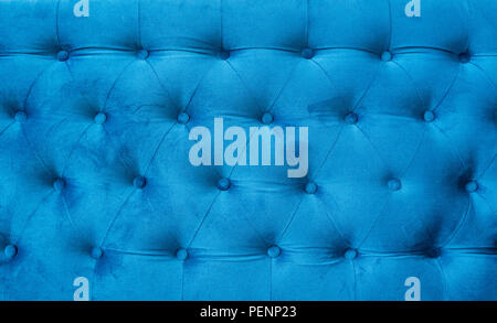 Velour surface of sofa close-up. Coach-type velours screed tightened with buttons. Blue chesterfield style quilted upholstery backdrop close up - Stock Photo