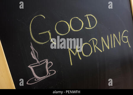 Good morning message with coffee cup written on blackboard. - Stock Photo