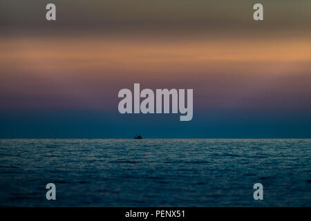 Vibrant sunset with blue clouds above horizon and small fishing boat, red, orange and deep blue colors, selective focus and long exposure blur on purp - Stock Photo