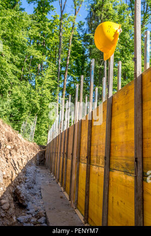 Construction Site Concept with a Bright Yellow Hard Hat Hanging on Post of Unfinished Building Foundation Under Construction in Wooded Forest Area. - Stock Photo