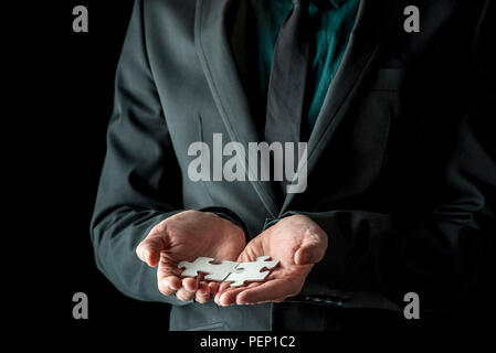 Businessman in black suit and tie holding two matching puzzle pieces, isolated on black background with copy space. - Stock Photo