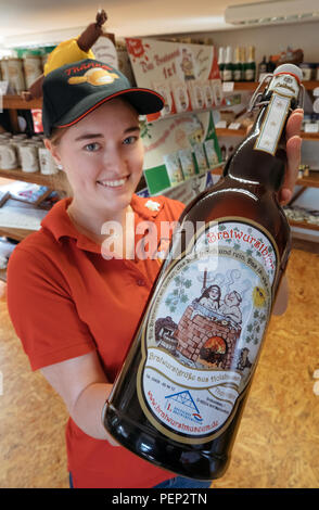 Holzhausen, Germany. 16th Aug, 2018. Saleswoman Celine Knaut shows a bottle of 'Bratwurstbier' in the Bratwurst Museum. Fans of this Thuringian speciality intend to celebrate the 'International Day of the Bratwurst' with new attractions in the Bratwurst Museum every year from today onwards. Credit: Arifoto Ug/Michael Reichel/dpa-Zentralbild/dpa/Alamy Live News - Stock Photo