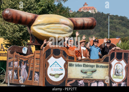 Holzhausen, Germany. 16th Aug, 2018. A giant bratwurst model accompanied by traditional figures roll into the Bratwurst Museum on a special cart. Fans of this Thuringian speciality intend to celebrate the 'International Day of the Bratwurst' with new attractions in the Bratwurst Museum every year from today onwards. Credit: Arifoto Ug/Michael Reichel/dpa-Zentralbild/dpa/Alamy Live News - Stock Photo