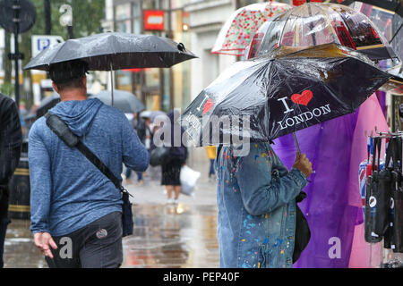 Piccadilly Circus. London. 16 Aug 2018. UK Weather: - Tourists shelter from the rain beneath umbrellas during heavy downpour in the capital.   Credit: Dinendra Haria/Alamy Live News - Stock Photo