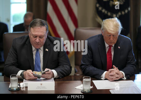 Washington DC, USA. 16th August 2018. - United States Secretary of State Mike Pompeo, left, reads a prayer as he sits next to US President Donald J. Trump during a Cabinet Meeting in the Cabinet Room of the White House. Credit: Oliver Contreras/CNP/ZUMA Wire/Alamy Live News - Stock Photo