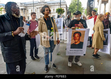London, UK. 16th August 2018. Protesters hold a vigil outside the South African High Commission in Trafalgar Square on the 6th anniversary of the massacre when 34 striking miners were shot dead by South African police at Lonmin's Marikana platinum mine. After speeches about the event, the names of the 34 victims were read and large photographs of them put on the front of the embassy along with flowere. Although evidence against the police was clear, 19 strikers were changed with murder and others imprisoned for other offences. Credit: Peter Marshall/Alamy Live News - Stock Photo