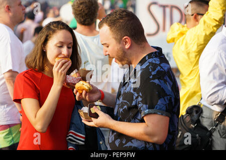New York, USA. 16th Aug, 2018. A couple eat burgers at Time Out New York's Battle of the Burger 2018 in New York, the United States, on Aug. 16, 2018. Over 100 people attended the event on Thursday to taste and vote for their favorite burgers made by burger vendors across the city. Credit: Lin Bilin/Xinhua/Alamy Live News - Stock Photo