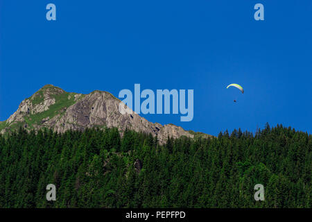 Paraglider flying over a mountain ridge in the Alps of the Jungfrau region in summer. Bernese Oberland, Switzerland - Stock Photo