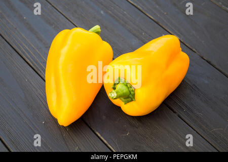 Yellow pepper on a black wooden background