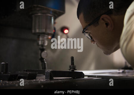 Tech. Sgt. Ryan Miller, 455th Expeditionary Maintenance Squadron Fabrication Flight aircraft metals technology craftsman, an Air Reserve technician deployed from Joint Base McGuire–Dix–Lakehurst, N.J., checks a piece of metal being cut in a computer numerical control machine at Bagram Air Field, Afghanistan, Jan. 18, 2016. The CNC machine can create complex aircraft components from raw metal that would normally be impossible to make conventionally. (U.S. Air Force photo/Tech. Sgt. Robert Cloys) - Stock Photo