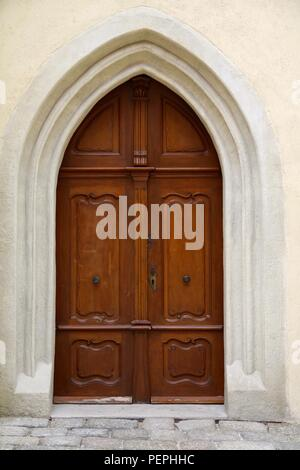 Double wooden doors in an arched doorway - Stock Photo