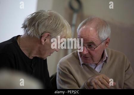Older gentlemen talking and sharing stories - Stock Photo
