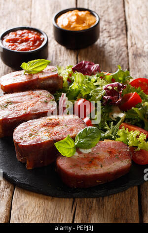Spicy roast pork brisket and fresh vegetable salad are served ketchup and mustard on the table. vertical - Stock Photo