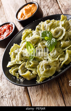Spinach cappelletti, ravioli, tortellini stuffed with meat with Parmesan cheese and basil served with sauces close-up on the table. vertical - Stock Photo