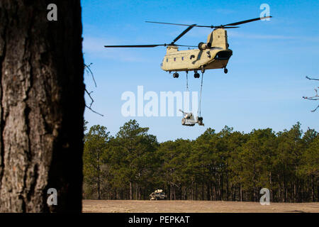 A CH-47 Chinook with the 3rd General Support Aviation Battalion, 82nd Combat Aviation Brigade, lifts a two-ton M119A3 light howitzer assigned to the 3rd Battalion, 319th Airborne Field Artillery Regiment, 82nd Airborne Division Artillery. The M119A3 is part of an air assault during a Division Artillery Readiness Test on Fort Bragg, N.C., Jan. 20. (U.S. Army photo by Capt. Adan Cazarez) - Stock Photo
