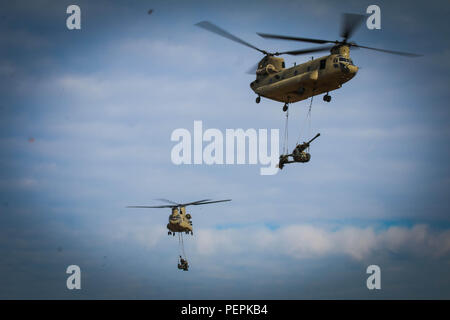 Two of three CH-47 Chinook with the 3rd General Support Aviation Battalion, 82nd Combat Aviation Brigade, transport M119A3 howitzers assigned to the 3rd Battalion, 319th Airborne Field Artillery Regiment, 82nd Airborne Division Artillery, during an air assault in support of a Division Artillery Readiness Test on Fort Bragg, N.C., Jan. 21. (U.S. Army photo by Capt. Adan Cazarez) - Stock Photo