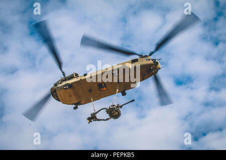 A CH-47 Chinook with the 82nd Combat Aviation Brigade, lifts a two-ton M119A3 light howitzer assigned to the 3rd Battalion, 319th Airborne Field Artillery Regiment, 82nd Airborne Division Artillery. The M119A3 is part of an air assault during a Division Artillery Readiness Test on Fort Bragg, N.C., Jan. 20. (U.S. Army photo by Capt. Adan Cazarez) - Stock Photo