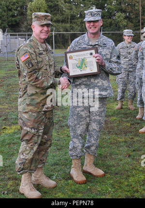 Col. Jon Drushal, I Corps chemical officer, presents Chief Warrant Officer 3 Russell Houser, commander of the 56th Army Band, with a certificate of appreciation for the chemical, biological, radiological, nuclear shop of the quarter on Joint Base Lewis-McChord, Wash., Jan. 20, 2016. I Corps chemical office implemented a way of recognizing units on JBLM that meet the readiness standards for chemical, biological, radiological and nuclear equipment during the Corps Logistics Command Maintenance Evaluation Training assessments. (U.S. Army photo by Sgt. Eliverto V. Larios) - Stock Photo