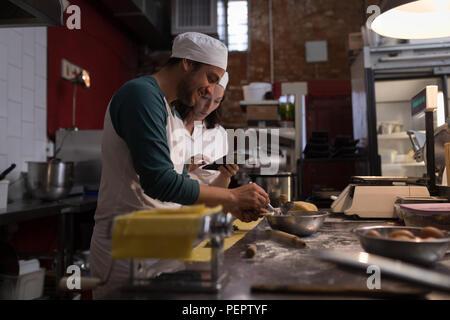 Baker preparing pasta while co-worker using digital tablet his beside - Stock Photo