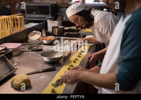 Bakers preparing pasta in bakery - Stock Photo