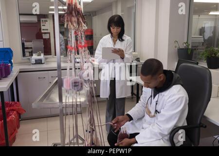 Laboratory technician analyzing blood bag - Stock Photo