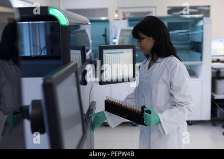 Laboratory technician holding test tubes - Stock Photo