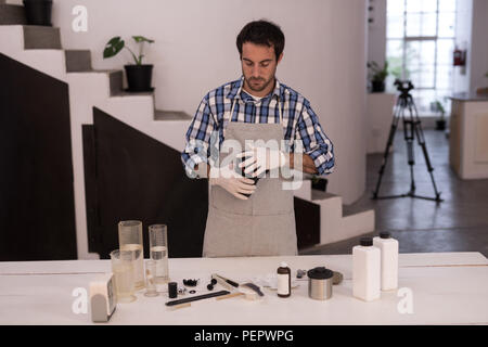 Male photographer opening a lens cover - Stock Photo