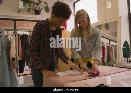 Fashion designers working on fabric - Stock Photo