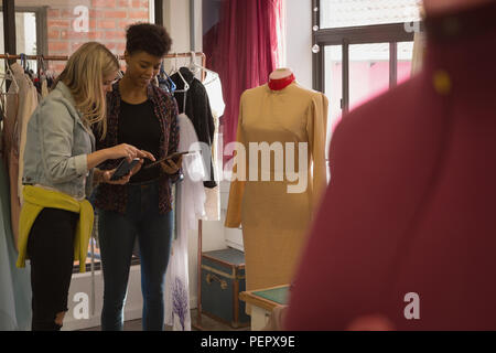 Fashion designers discussing on digital tablet - Stock Photo
