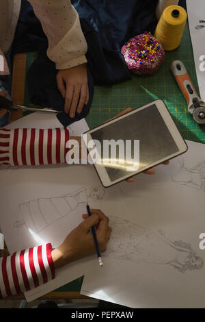 Fashion designers drawing a sketch using digital tablet in fashion studio - Stock Photo