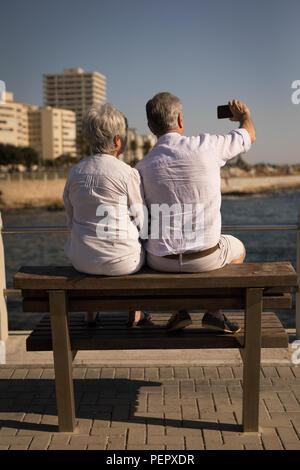 Senior couple taking selfie while sitting on bench at promenade - Stock Photo