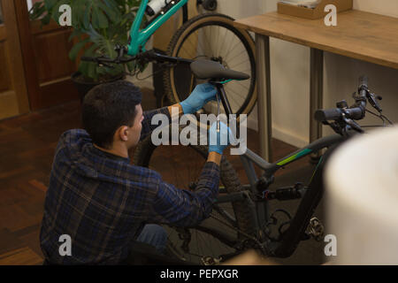 Man adjusting bicycle seat with spanner in workshop - Stock Photo