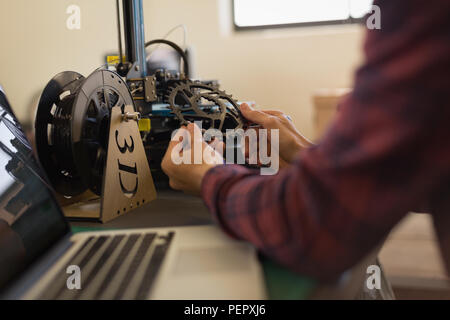 Mechanic checking bicycle chain ring on table - Stock Photo
