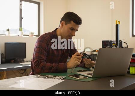Mechanic checking diameter of chain ring with vernier calipers - Stock Photo