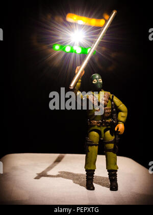 Creative, conceptual photo of a toy soldier holding the Indian Flag made using LED light strips and lens flare created from artificial white light. - Stock Photo