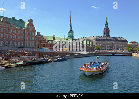 Canal cruise boat in Slotsholm Canal in Copenhagen. Christiansborg Castle, the Parliament,  the old stock exchange and dockside cafe and kayak rental. - Stock Photo