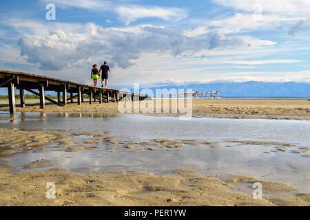 A couple walking over Wooden bridge leading to Famous Queens Beach in Nin near Zadar, Croatia. Rare sand beach in the Adriatic sea, popular for surfin - Stock Photo