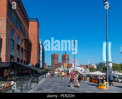 Cafes, bars, restaurants and shops on Stranden, in the harbour area, looking towards Rådhusplassen and City Hall, Aker Brygge, Oslo, Norway - Stock Photo