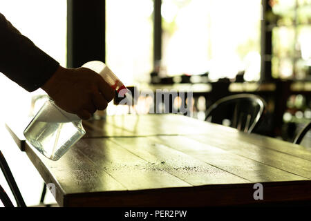 Silhouette waiter cleaning the table with disinfectant spray in a restaurant. - Stock Photo