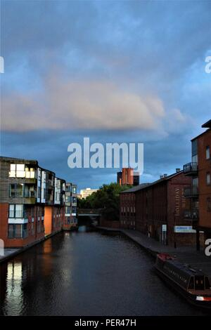 Birmingham England canal view in the early hours of the morning with a beautiful blue sky, white clouds and residential buildings along the canal - Stock Photo