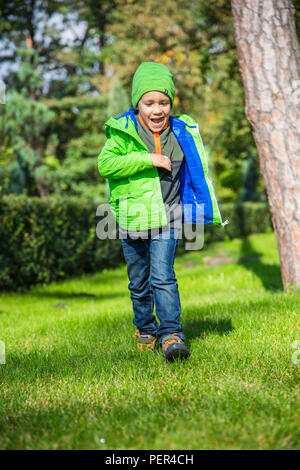 A child runs along the green grass in park in spring. - Stock Photo