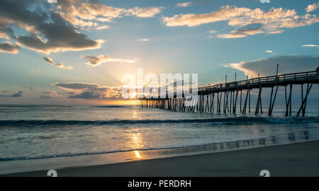 Day breaks over the Atlantic Ocean with a dramatic morning sky and calm sea. A fishing pier extends out into the water. Sunrise reflected on the ocean. - Stock Photo