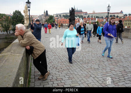 Tourists walking on across on The Charles Bridge - Stock Photo