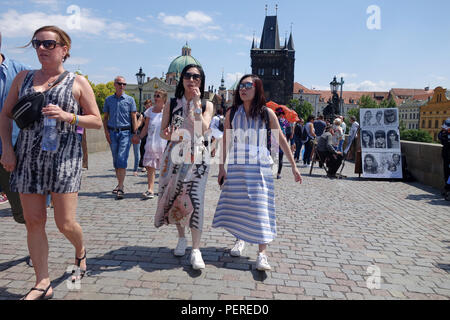 Tourists walking on across on The Charles Bridge, Prague, Czech Republic - Stock Photo
